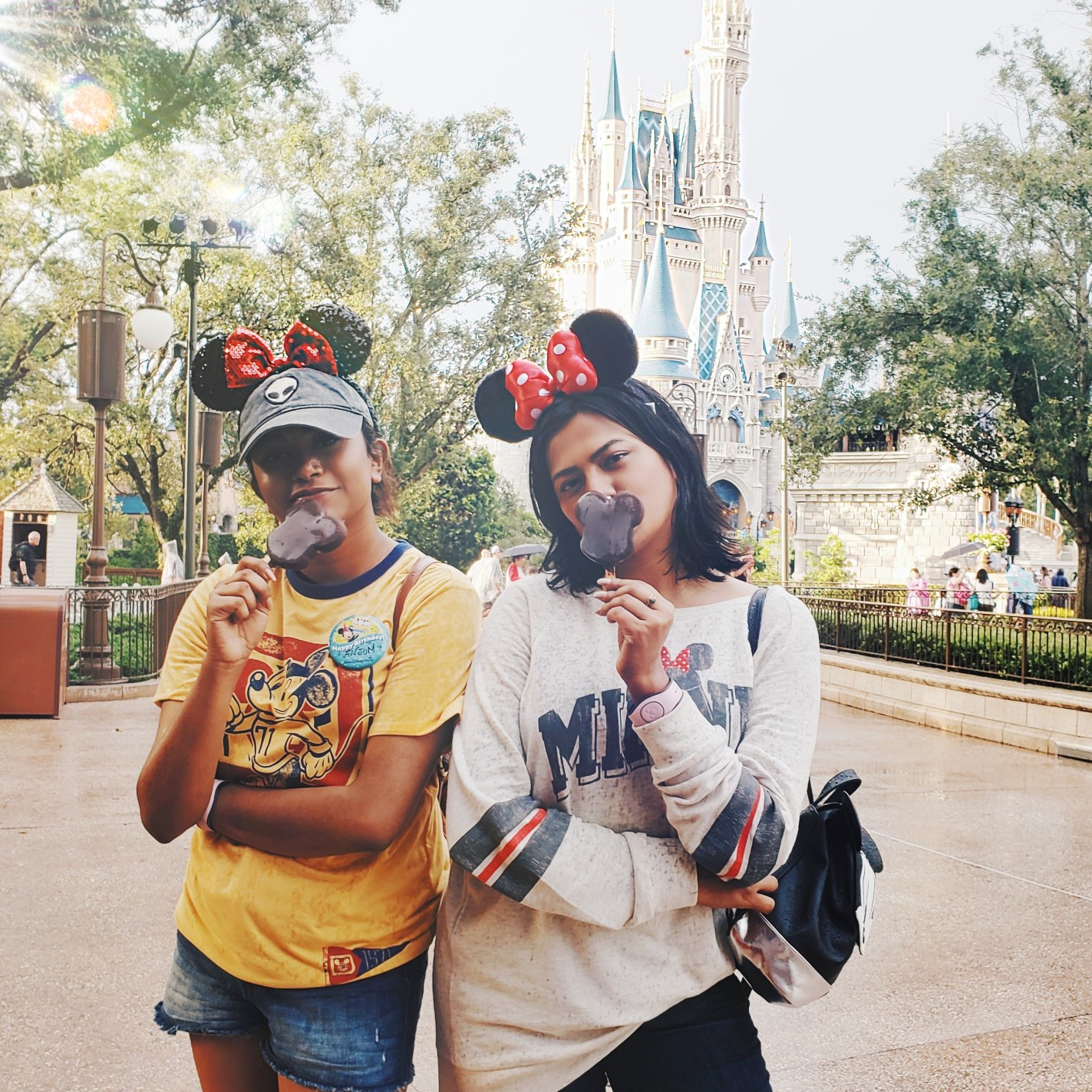 Sisters Posing In front of Cinderella Castle with Mickey Ears Ice Cream