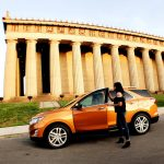 An orange car in front of Parthenon