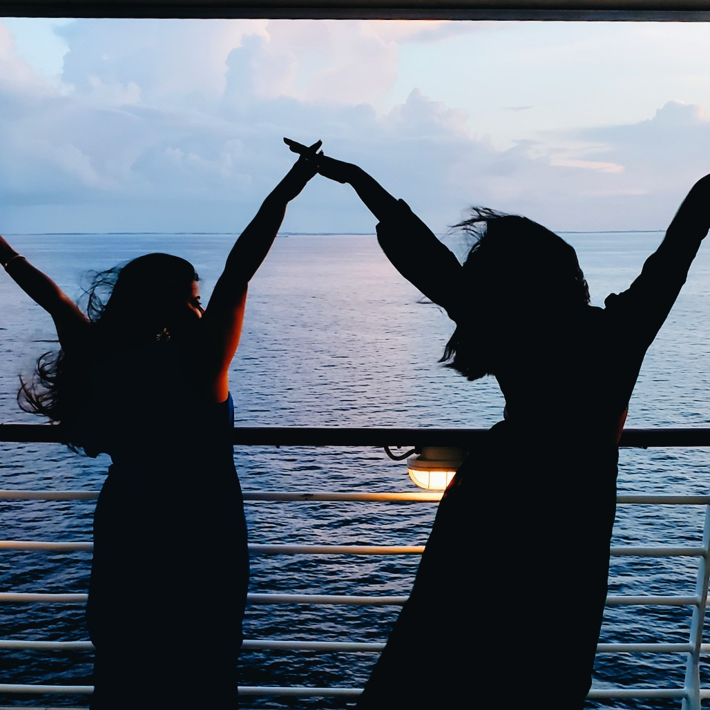 Silhouettes of two girls on a ship by the ocea