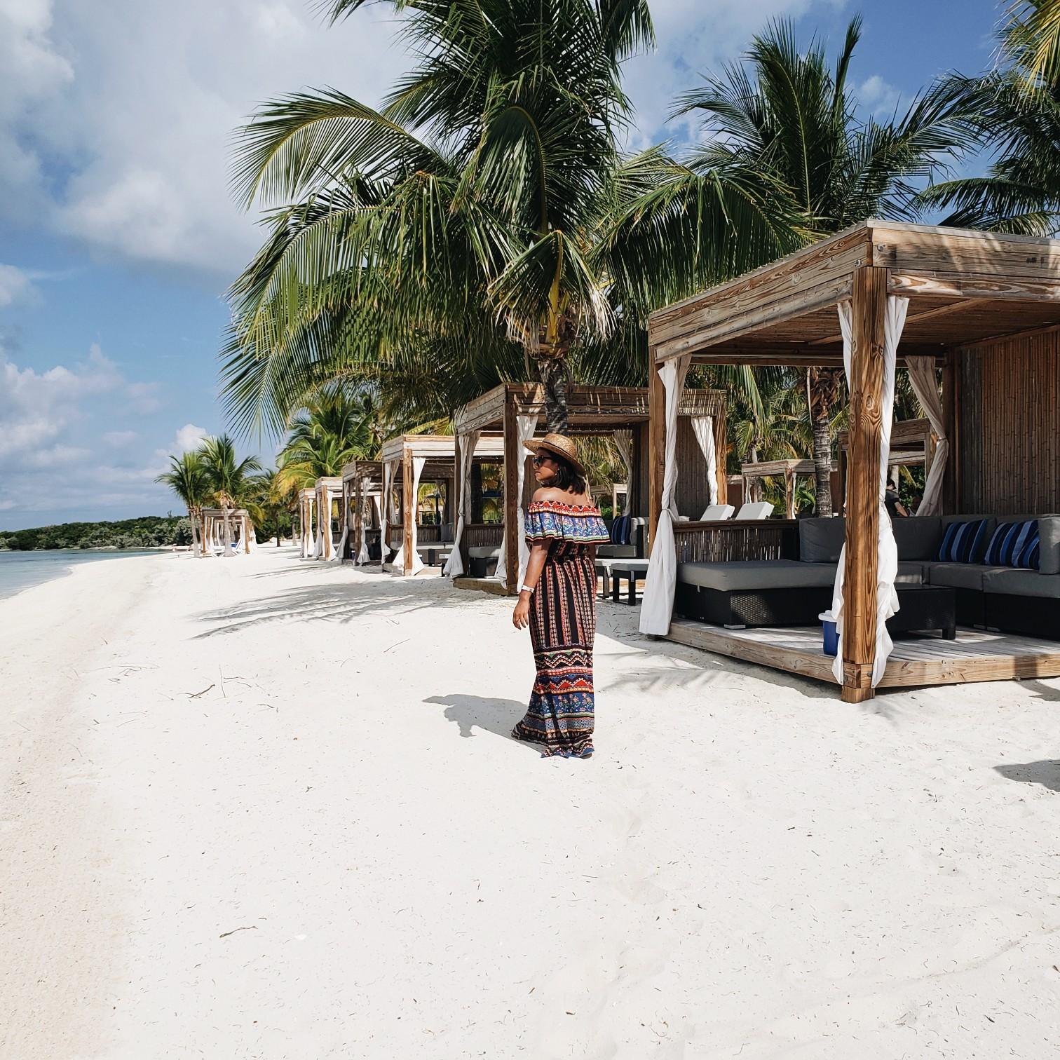 Travel Blogger Afroza Khan walking on beach near private cabanas in Bahamas