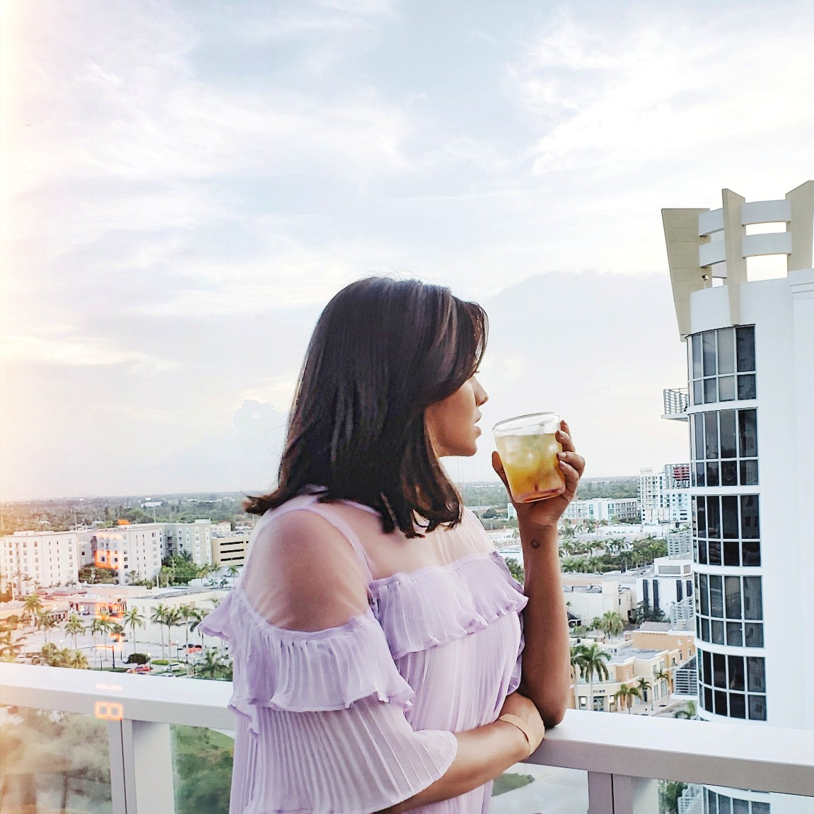 Girl in pale purple dress drinking yellow orange drink on rooftop bar