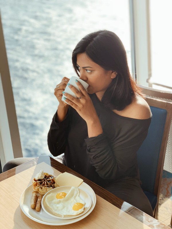 Miami Fashion Travel Lifestyle Blogger Afroza Khan eating breakfast in Royal Caribbean Symphony of the Seas windjammer sipping coffee