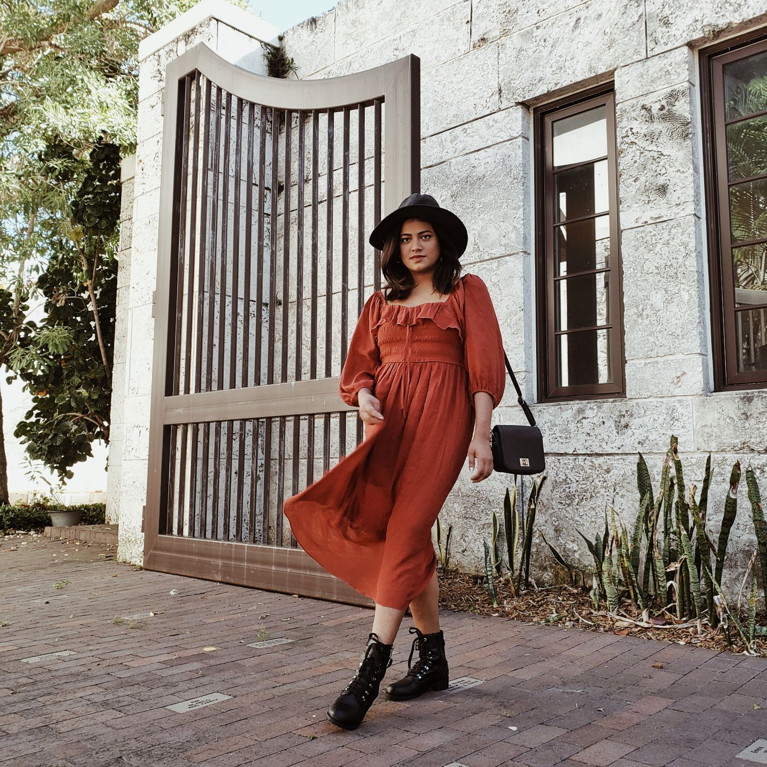 Miami blogger wearing burnt orange boho long maxi dress with black hat and combat boots