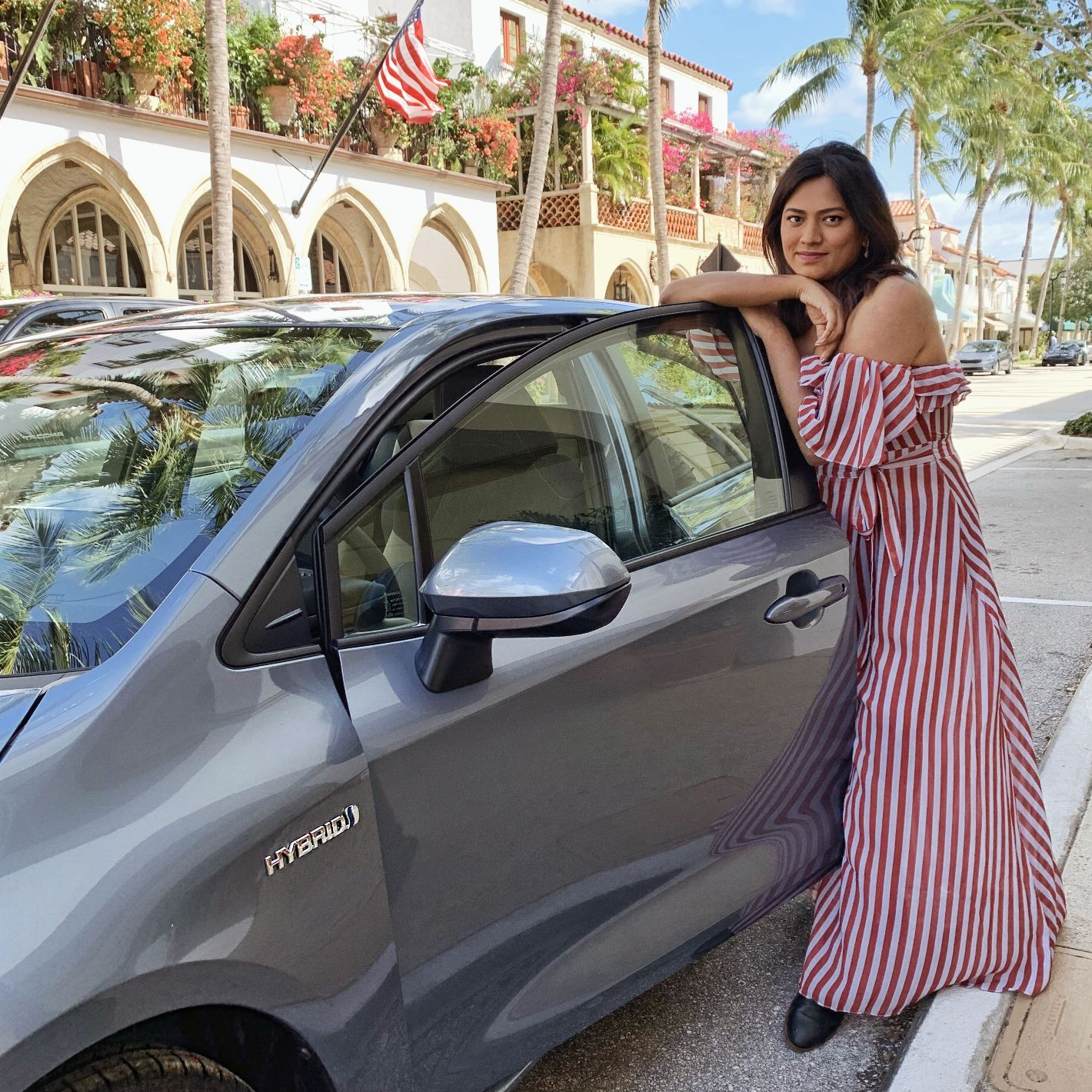 Miami Blogger Afroza Khan Wearing Red & White Stripe Dress Next to Toyota Hybrid