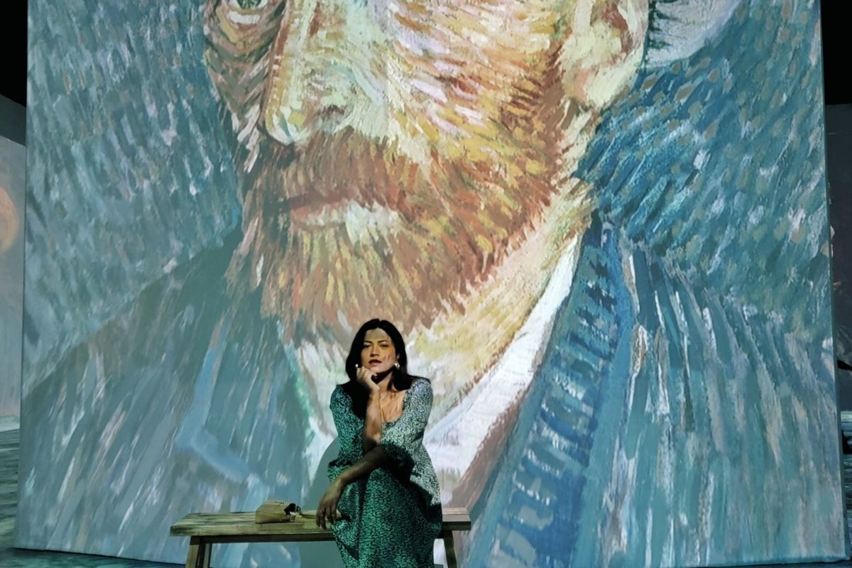 Miami Blogger wearing a boho dress sitting in front of Van Gogh Self-portrait at Beyond Van Gogh Miami
